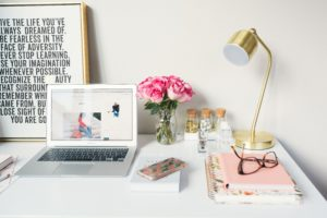 A lovely desk with an open laptop showing a blog website